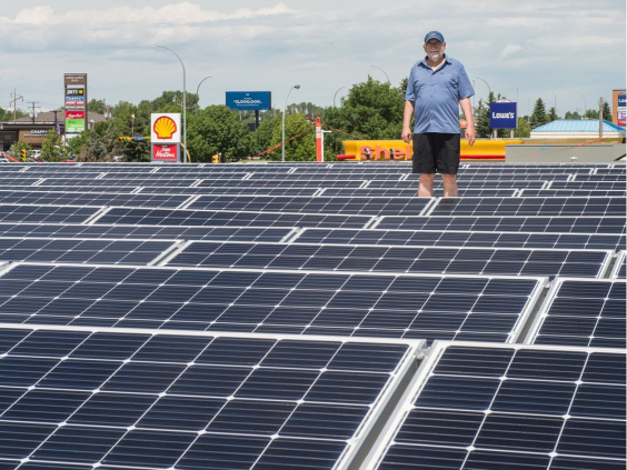 John Brazill, director of large scale solar projects with Wascana Solar Co-operative, stands among solar panels on the roof of the Conexus Credit Union North Albert branch. BRANDON HARDER / Regina Leader-Post
